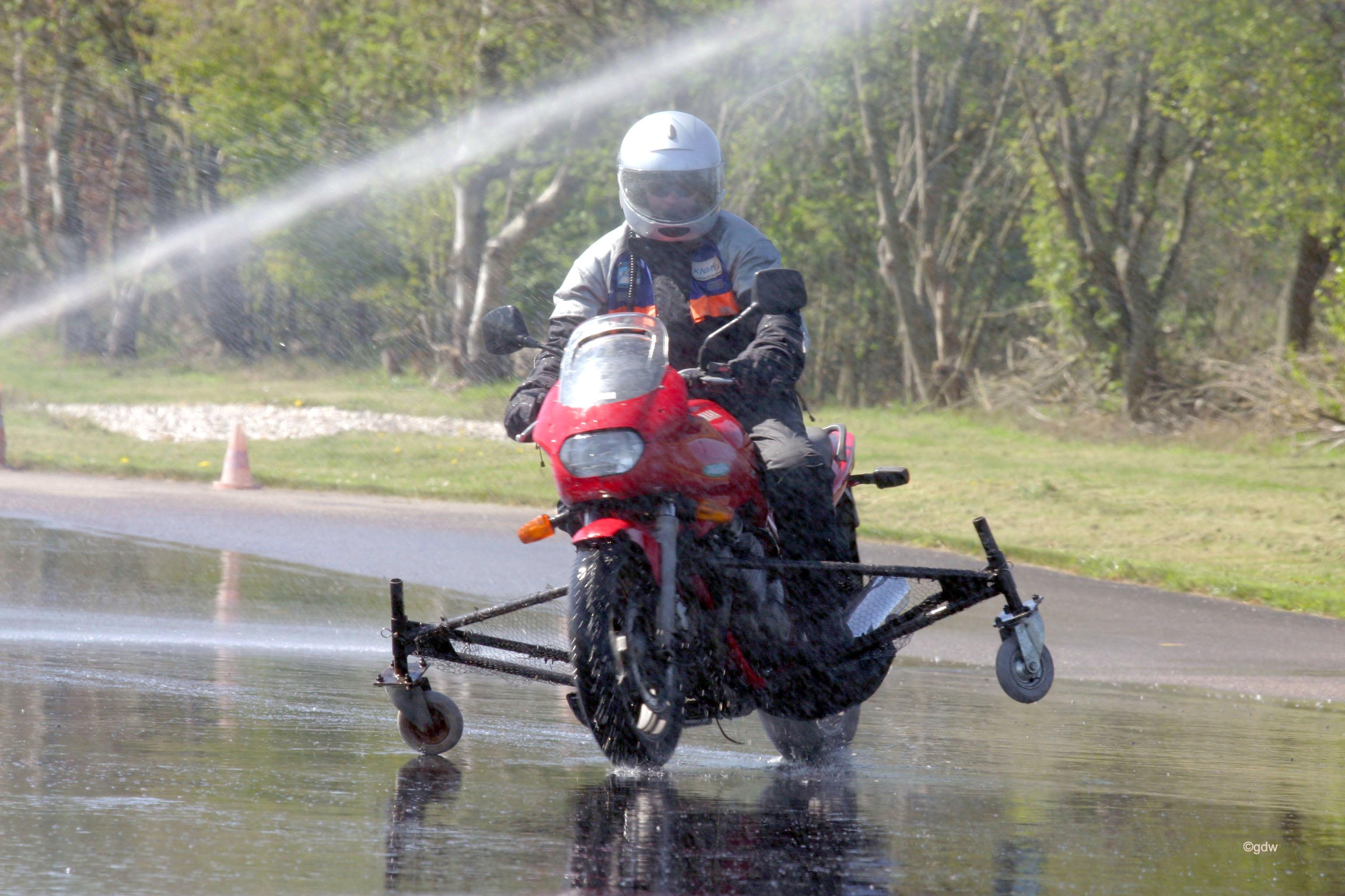 De slipcursus waarbij de motorrijder op een motor van DIBO met zijwielen op het slipvlak aan het glijden is